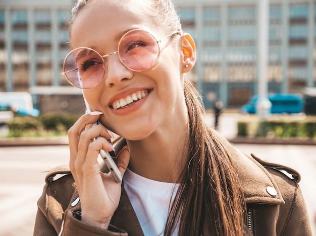 Porträt der jungen schönen lächelnden frau, die am telefon spricht modisches mädchen in der zufälligen sommerkleidung lustige und positive frau, die auf der straße aufwirft Kostenlose Fotos