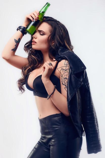 Porträt der jungen sexy frau mit langen haaren in der lederjacke, die flasche bier hält Kostenlose Fotos