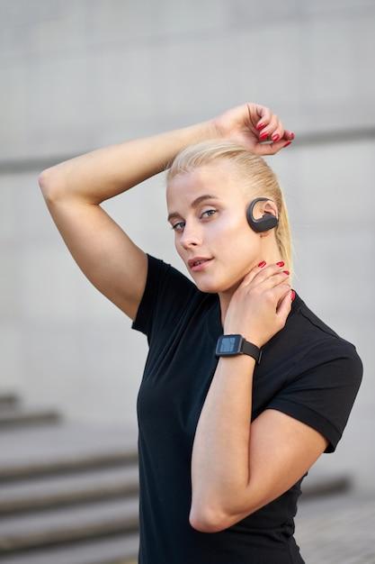Porträt der jungen sportlichen frau, die schwarzes hemd trägt und hören musik. außenaufnahme auf grauem wandhintergrund. Premium Fotos