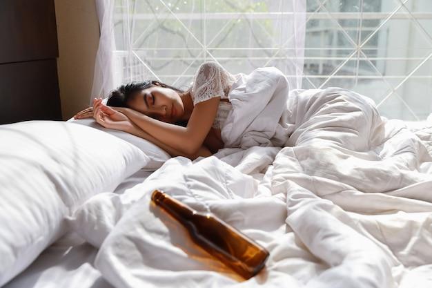 Porträt der jungen und schönen betrunkenen asiatischen frau in weißen dessous nachtwäsche bewusstlos im bett, nachdem zu viel alkohol von der party getrunken wurde. lange haare der jungen frau, die auf bett im schlafzimmer liegen und spät aufwachen Premium Fotos