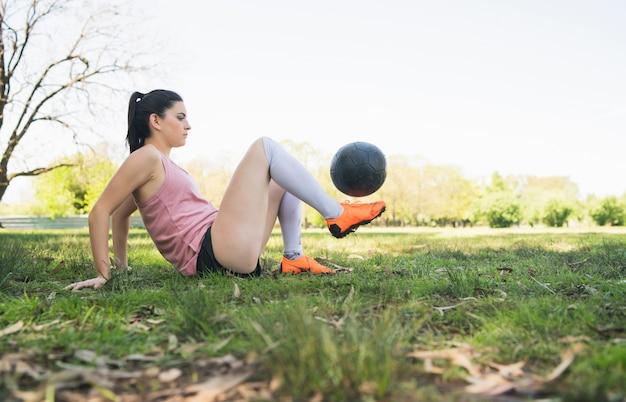 Porträt der jungen weiblichen fußballspielerin, die fähigkeiten auf dem fußballplatz trainiert und übt. sportkonzept. Kostenlose Fotos