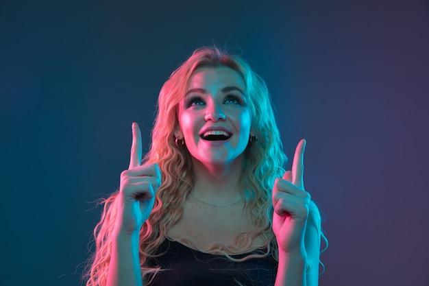Porträt der kaukasischen jungen frau auf gradientenraum im neonlicht Kostenlose Fotos