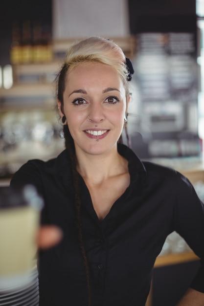 Porträt der kellnerin stehend mit wegwerfkaffeetasse Kostenlose Fotos