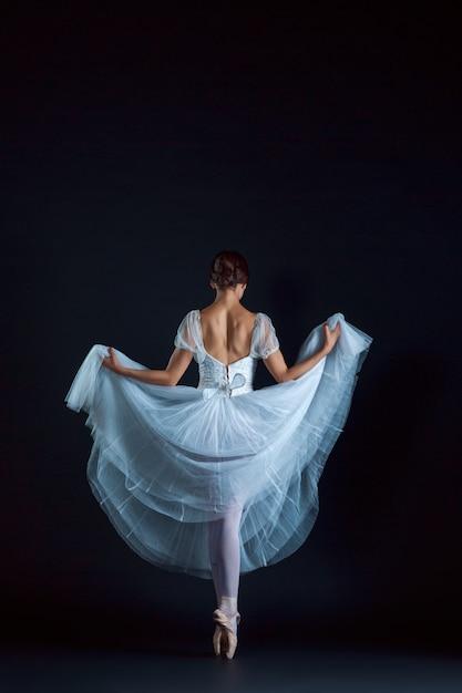 Porträt der klassischen ballerina im weißen kleid auf schwarzer wand Kostenlose Fotos
