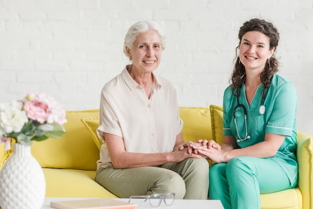 Porträt der krankenschwester sitzend mit älterem weiblichem patienten auf sofa Kostenlose Fotos