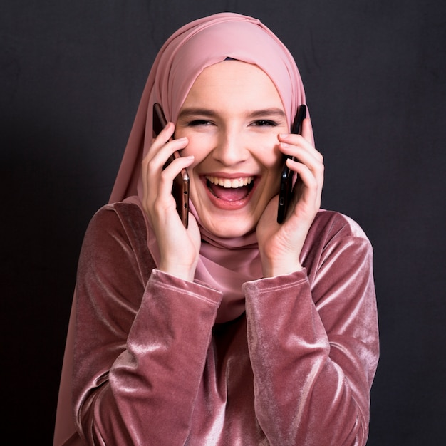 Porträt der lachenden frau kamera bei der unterhaltung betrachtend auf mobiltelefon Kostenlose Fotos