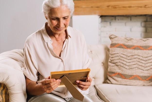 Porträt der lächelnden älteren frau, die auf dem sofa betrachtet fotorahmen sitzt Kostenlose Fotos