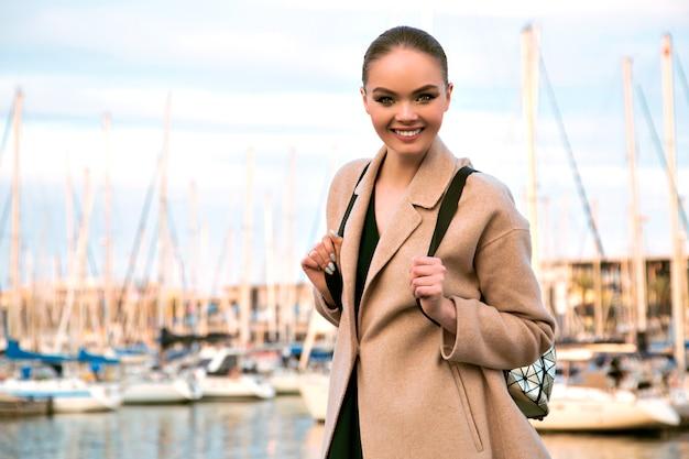 Porträt der lächelnden eleganten prächtigen frau, die nahe luxusyachtclub aufwirft, beigen kaschmirmantel und rucksack tragend, touristische, warme pastellfarbene farben trägt. Kostenlose Fotos