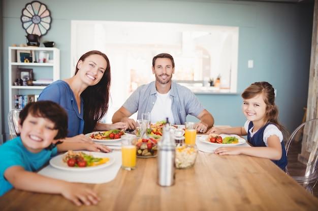 Porträt der lächelnden familie mit lebensmittel auf speisetische Premium Fotos
