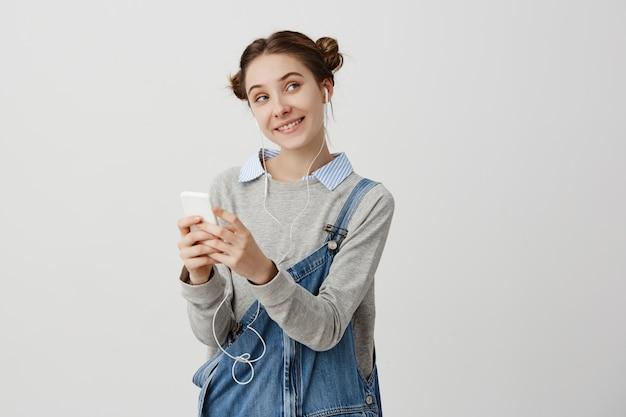 Porträt der lächelnden frau im jeansoverall, der seitwärts mit den kniffligen augen schaut. mit kopfhörern. lustige weibliche büroangestellte, die mit ihrem kollegen plaudert, der flirtend ist. positive gefühle Kostenlose Fotos