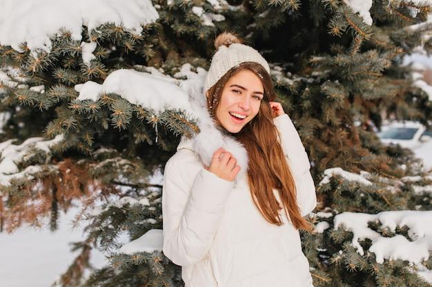 Porträt der lächelnden frau im warmen weißen mantel, der neben baum in frostigem tag aufwirft. foto im freien der romantischen dame mit den langen haaren, die vor der schneebedeckten fichte während des winterfotoshootings stehen. Kostenlose Fotos