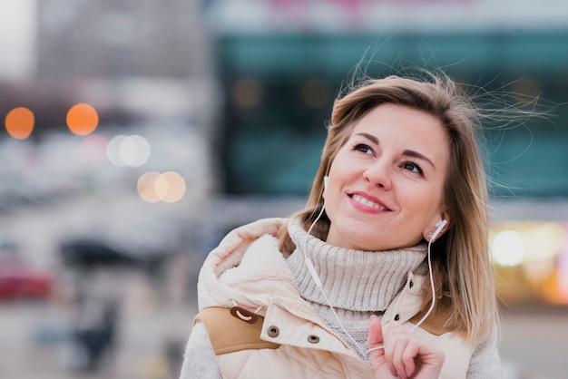 Porträt der lächelnden frau mit kopfhörern auf dach Kostenlose Fotos