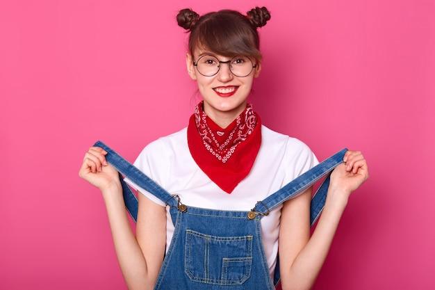 Porträt der lächelnden frau mit lustigen bündeln, trägt t-shirt, jeansoverall und kopftuch am hals, hat zahniges lächeln Kostenlose Fotos