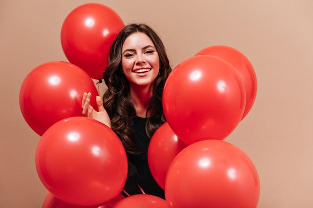 Porträt der lächelnden frau mit welligem dunklem haar, das mit riesigen luftballons auf beigem hintergrund aufwirft. Kostenlose Fotos