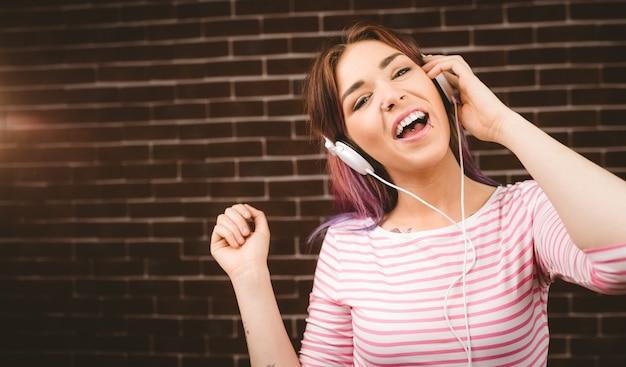 Porträt der lächelnden hörenden musik der frau auf kopfhörern Premium Fotos