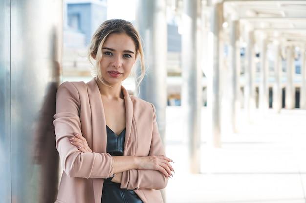 Porträt der lächelnden hübschen jungen geschäftsfrau mit verschränkten armen auf bürohintergrund. Premium Fotos