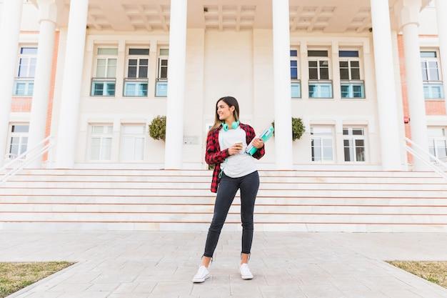 Porträt der lächelnden jugendstudentin, die bücher und die mitnehmerkaffeetasse stehen vor universitätsgebäude hält Kostenlose Fotos