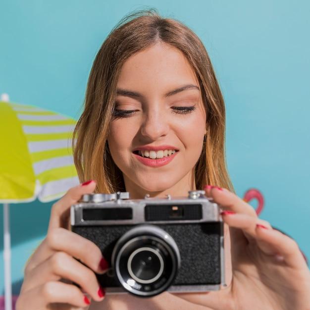 Porträt der lächelnden jungen frau, die fotos auf kamera macht Kostenlose Fotos