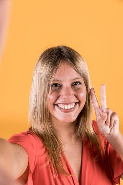 Porträt der lächelnden jungen frau, die friedenszeichen zeigt Kostenlose Fotos