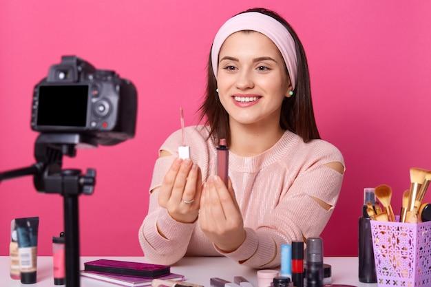 Porträt der lächelnden jungen frau, die lippenstift zur kamera zeigt Kostenlose Fotos