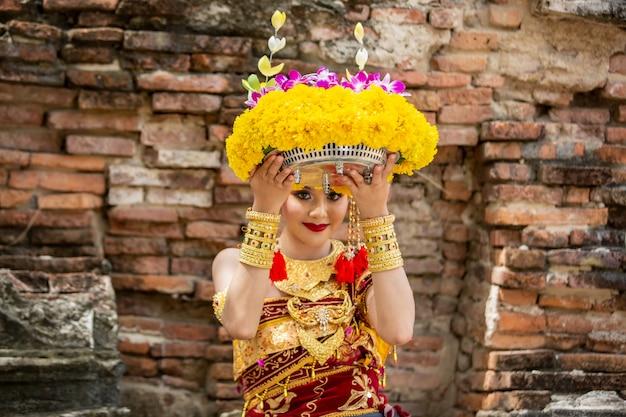 Porträt der lächelnden jungen frau in der balinesischen traditionellen kleidung, die blumen-blumenstrauß am tempel hält Premium Fotos
