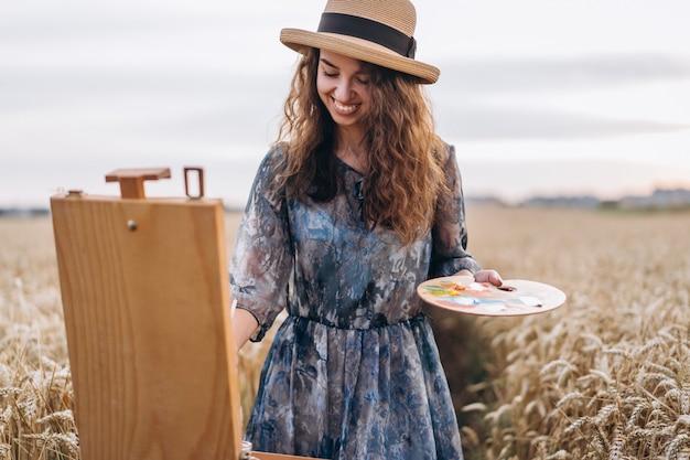 Porträt der lächelnden künstlerin mit dem lockigen haar im hut. mädchen zeichnet ein bild einer landschaft in einem weizenfeld Premium Fotos