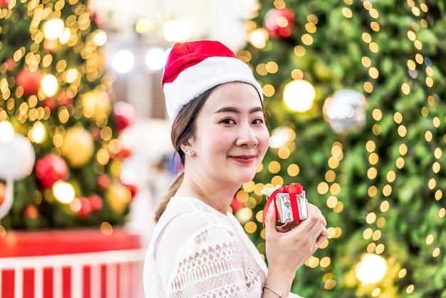 Porträt der lächelnden schönen jungen asiatischen frau mit geschenk auf dem festlichen weihnachtsmarkt Premium Fotos