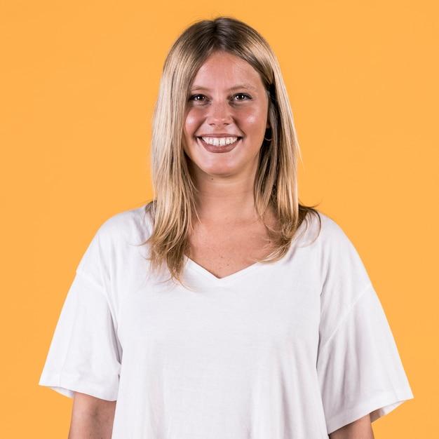 Porträt der lächelnden sperrungsfrau, die auf farbigem hintergrund steht Kostenlose Fotos
