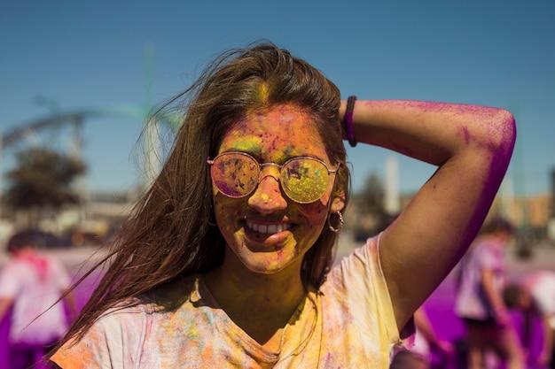 Porträt der lächelnden tragenden sonnenbrille der jungen frau bedeckt mit holi farbe Kostenlose Fotos