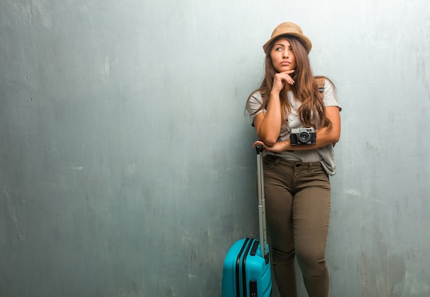 Porträt der lateinischen frau des jungen reisenden gegen eine wand, die oben denkt und schaut Premium Fotos