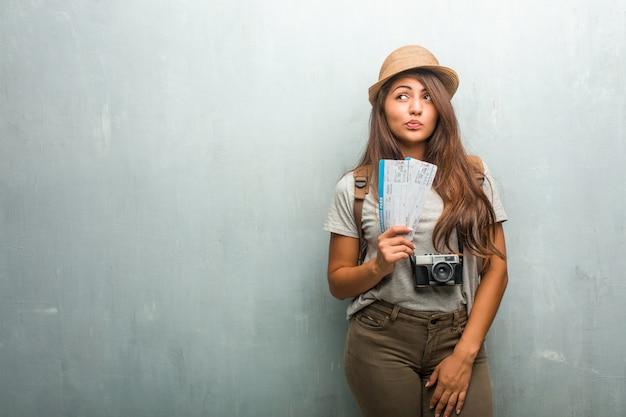 Porträt der lateinischen frau des jungen reisenden gegen eine wand zweifelnd und verwirrt, an eine idee denkend oder an etwas gesorgt. Premium Fotos