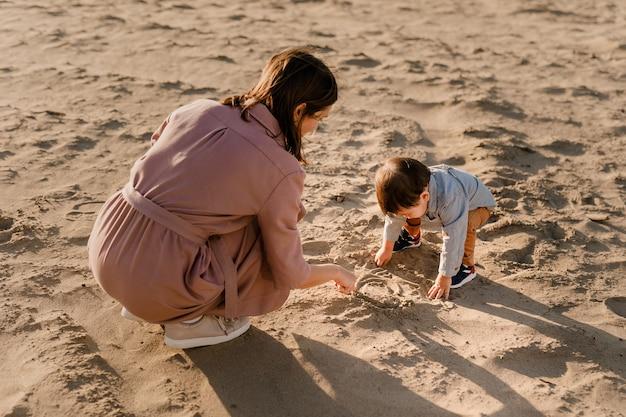 Porträt der liebenden mutter und seines einjährigen sohnes, der mit sand geht und spielt. Premium Fotos