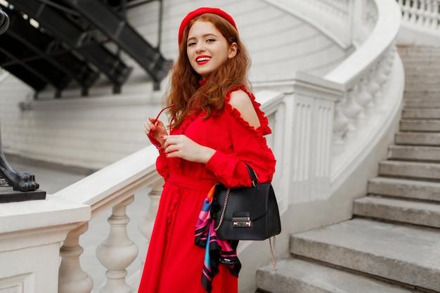 Porträt der modischen ingwerfrau in der roten baskenmütze und im eleganten kleid, das im freien aufwirft. Kostenlose Fotos