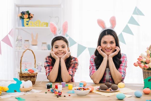 Porträt der mutter und ihrer tochter, die osterhasenohren tragen, die auf tabelle mit ostern-schokoladen sich lehnen Kostenlose Fotos