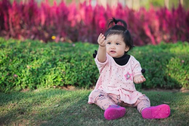 Porträt der netten babyreise am blumengarten Premium Fotos