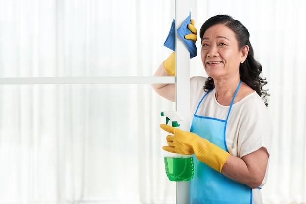 Porträt der netten haushälterin aufwerfend an der glastrennwand mit reinigungsmittelspray Kostenlose Fotos