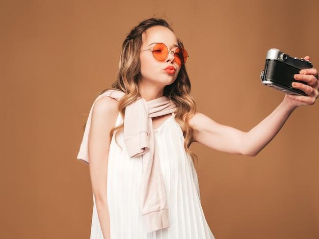 Porträt der netten jungen frau, die foto mit inspiration macht und weißes kleid trägt. mädchen, das retro- kamera anhält. model posing.making selfie Kostenlose Fotos