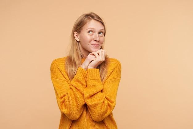 Porträt der niedlichen jungen rothaarigen frau mit natürlichem make-up, das gefaltete hände unter ihrem kinn hält und positiv nach oben schaut, lokalisiert auf beige Kostenlose Fotos