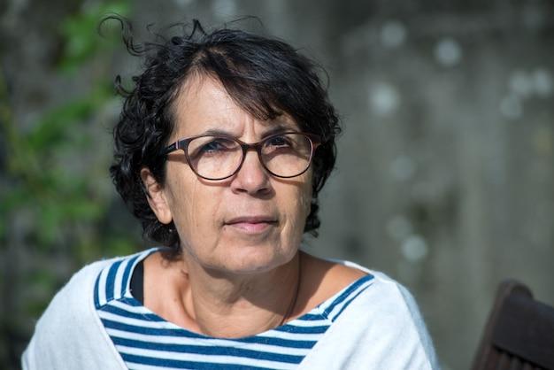 Porträt der reifen frau des brunette mit brillen Premium Fotos