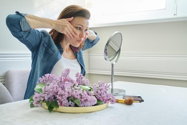 Porträt der reifen frau mit make-upspiegel ihr gesicht und hals massierend Premium Fotos