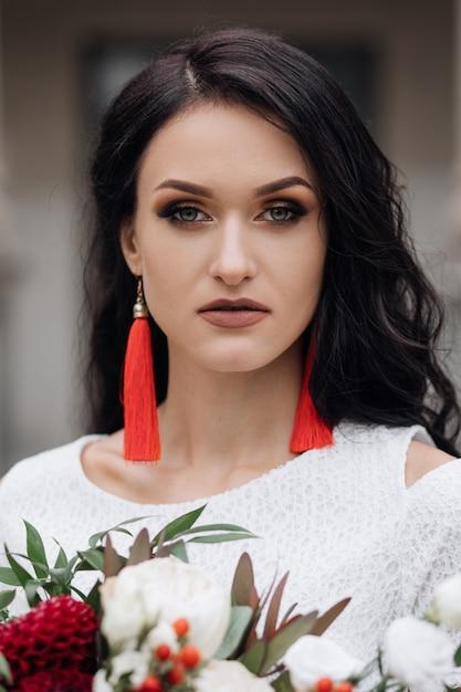 Porträt der reizend brunettebraut im weißen kleid mit rotem zubehör Kostenlose Fotos