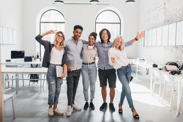 Porträt der schlanken büroangestellten in voller länge in jeans, die mit gekreuzten beinen nahe asiatischer kollegin stehen. innenfoto des großen afrikanischen studenten und der glücklichen europäischen frau mit laptop. Kostenlose Fotos