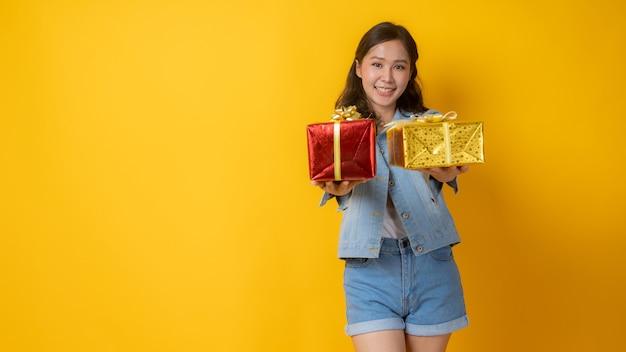 Porträt der schönen asiatischen frau in jeanskleidern, die geschenkbox halten Premium Fotos