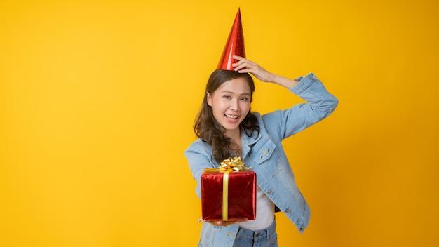 Porträt der schönen asiatischen frau legte roten hut auf kopf, geschenkbox haltend Premium Fotos