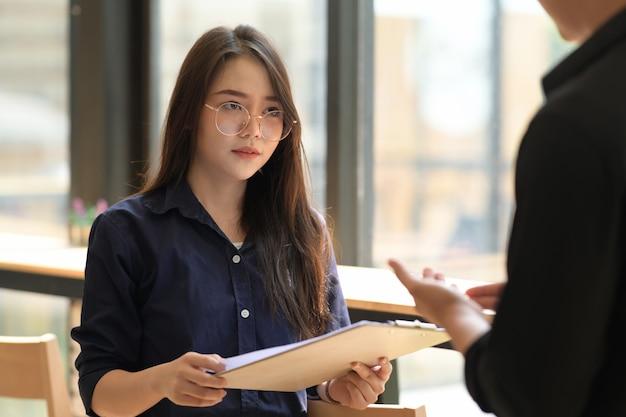 Porträt der schönen asiatischen geschäftsfrau, die schreibarbeit beim treffen hält Premium Fotos