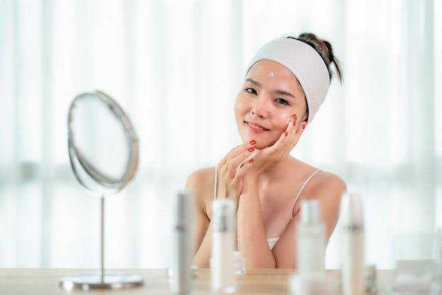 Porträt der schönen asiatischen jungen frau, die von ihrer haut sitzt nahe spiegel im schlafzimmer mit hautpflegeflasche auf tabelle, rührendes gesicht der frau sich interessiert. schönheits-jugend-hautpflege-konzept Premium Fotos