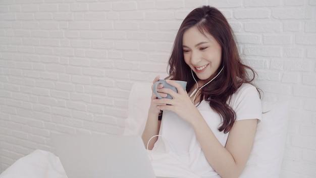 Porträt der schönen attraktiven asiatin, die computer verwendet Kostenlose Fotos