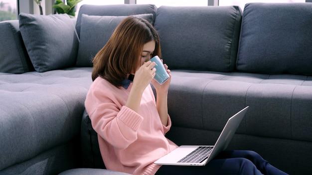 Porträt der schönen attraktiven asiatin, die den computer oder laptop hält einen warmen tasse kaffee oder einen tee verwendet Kostenlose Fotos