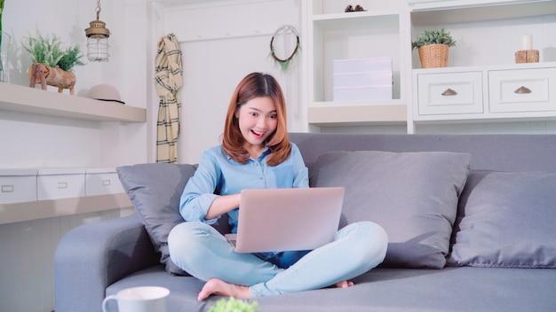Porträt der schönen attraktiven jungen lächelnden asiatin, die computer oder laptop verwendet Kostenlose Fotos