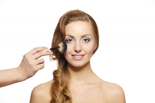 Porträt der schönen blonden frau mit dem langen haar und make-upbürste nahe attraktivem gesicht Kostenlose Fotos